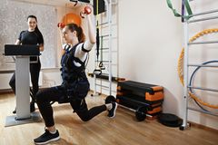 Lunge with EMS. Caucasian women makes lunge with weights in gym. Female trainer standing aside manages electric muscle stimulation purposed to increase Royalty Free Stock Photo