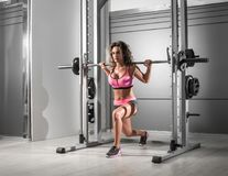 Lunges at Smith machine. Pretty slim fit female doing lunge exercise at Smith rack bar machine in modern fitness center. Toned image stock photo