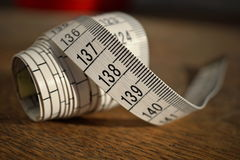 Lunghezza bianca di misurazione di nastro di misura di nastro nei metri e nei centimetri sulla superficie di legno come simbolo d Fotografie Stock Libere da Diritti