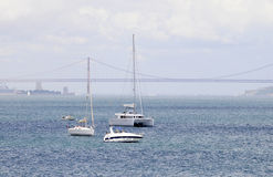 Lungomare di Lisbona: Yacht bianco, ponte rosso, torre di Belem Fotografia Stock