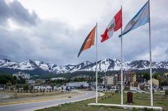 Lungomare di Ushuaia, con la bandiera dell'Argentina e le montagne nevose Immagini Stock