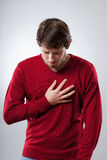 Lungs attack. Young man has a strong lungs pain holding his chest royalty free stock photography