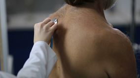 Lungs auscultation with stethoscope at clinic stock footage
