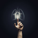 Lungs health. Male hand pointing on lung radiography on dark background stock images