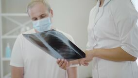 Lungs x-ray in female hands with unrecognizable doctor explaining roentgen to mid-adult man in face mask. Professional