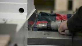 Luoghi di perforazione in una superficie di metallo facendo uso di un trapano elettrico tenuto in mano stock footage