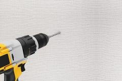 Luogo di perforazione ricaricabile e senza cordone giallo del trapano nella parete Immagini Stock Libere da Diritti