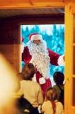 LUOSTO Finland - Januari 15, 2012: Barn som hälsar Santa Claus Royaltyfri Fotografi