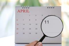 Lupa à disposição no calendário você pode olhar o dia onze de Fotos de Stock Royalty Free