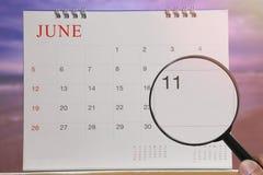 Lupa à disposição no calendário você pode olhar o dia onze de Imagens de Stock Royalty Free