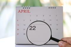 Lupa à disposição no calendário você pode olhar vinte e dois dias Foto de Stock