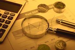 Lupa, calculadora, pluma, y moneda en gráfico financiero Fotos de archivo