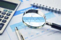 Lupa, calculadora y pluma en gráfico financiero Foto de archivo