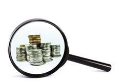 Lupa com o close up da moeda no fundo branco Imagens de Stock Royalty Free
