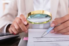 Lupa de Checking Invoice With de la empresaria imágenes de archivo libres de regalías