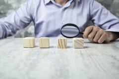 Lupa de la mano del hombre con los cubos de madera imagen de archivo libre de regalías