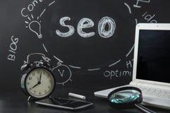 Lupa del concepto de la optimización del motor de SEO Search, reloj, smartphone en un fondo negro con una inscripción SEO Close p Imagen de archivo