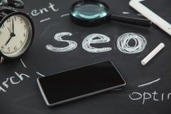 Lupa del concepto de la optimización del motor de SEO Search, reloj, smartphone en un fondo negro con una inscripción SEO Closeup imagen de archivo libre de regalías