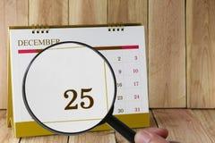 Lupa a disposición en calendario usted puede mirar veinticinco DA Fotografía de archivo