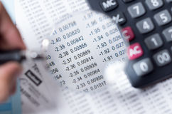 Lupa do close up sobre o papel com números Foto de Stock
