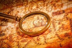 A lupa do vintage encontra-se em um mapa do mundo antigo Imagens de Stock
