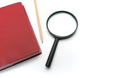 Lupa e caderno vermelho da tampa no fundo branco Fotos de Stock Royalty Free