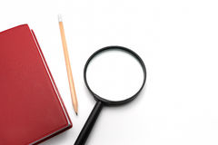 Lupa e caderno vermelho da tampa no fundo branco Imagem de Stock