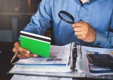 Lupa e calculadora do uso do homem de negócios para encontrar algo no livro de conta foto de stock royalty free