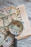 Lupa, el periódico y dólares americanos imágenes de archivo libres de regalías