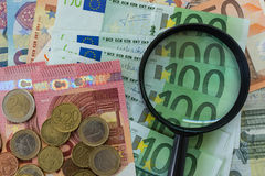 lupa en billetes de banco euro con las monedas euro como financieras Imagenes de archivo