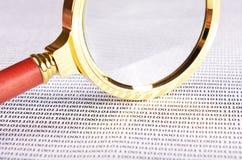 Lupa en el código digital Fotografía de archivo libre de regalías