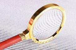 Lupa en el código digital Imagenes de archivo