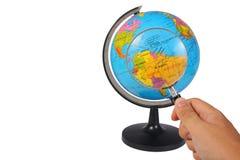 Lupa en el globo de la tierra en blanco Imágenes de archivo libres de regalías