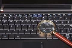 Lupa en el teclado Fotos de archivo libres de regalías