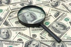Lupa en fondo del dinero Foto de archivo