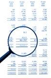 Lupa en la hoja de equilibrio financiero Imágenes de archivo libres de regalías
