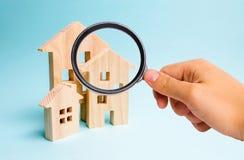 A lupa está olhando as três casas Comprando e vendendo de bens imobiliários, construção Apartamentos e apartamentos cidade imagens de stock royalty free