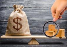 A lupa está olhando o grupo das caixas Saco do dinheiro nas escalas Equilíbrio de comércio conceptual entre países fotografia de stock royalty free