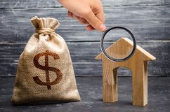 A lupa está olhando um saco com dinheiro e uma casa com uma grande entrada Conceito da aquisição dos bens imobiliários fotografia de stock