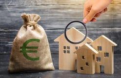 A lupa está olhando um saco com euro- dinheiro e três casas Empréstimo barato disponível, hipoteca Impostos, renda alugado imagem de stock royalty free