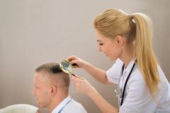 Lupa fêmea de Looking Hair Through do dermatologista Fotografia de Stock Royalty Free