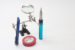 Lupa, gas soldering iron, scalpel and Insulating tape.  Stock Photos