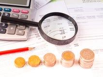 Lupa no balanço financeiro com calculadora e pilha de moedas Fotos de Stock