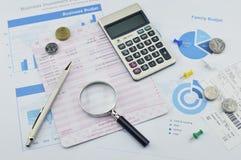 Lupa, pluma y moneda en el papel cuadriculado, concepto de ahorro Imágenes de archivo libres de regalías