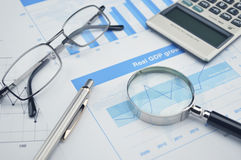 Lupa, pluma y vidrios en carta y gráfico financieros Imagen de archivo libre de regalías