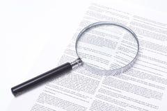 Lupa que encontra-se em um contrato legal Imagens de Stock