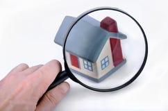 Lupa que examina una casa modelo. Foto de archivo libre de regalías
