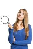 Mujer con la lupa que mira para arriba Imagen de archivo