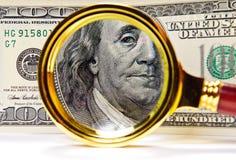 Lupa sobre el dinero Foto de archivo libre de regalías