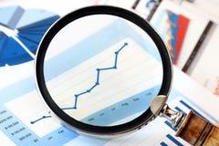 Lupa sobre o gráfico financeiro Imagens de Stock Royalty Free